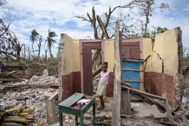 Ein Maedchen steht in den Truemmern ihres zerstoerten Hauses in einem kleinen Dorf nahe Les Cayes am 14.10.16.