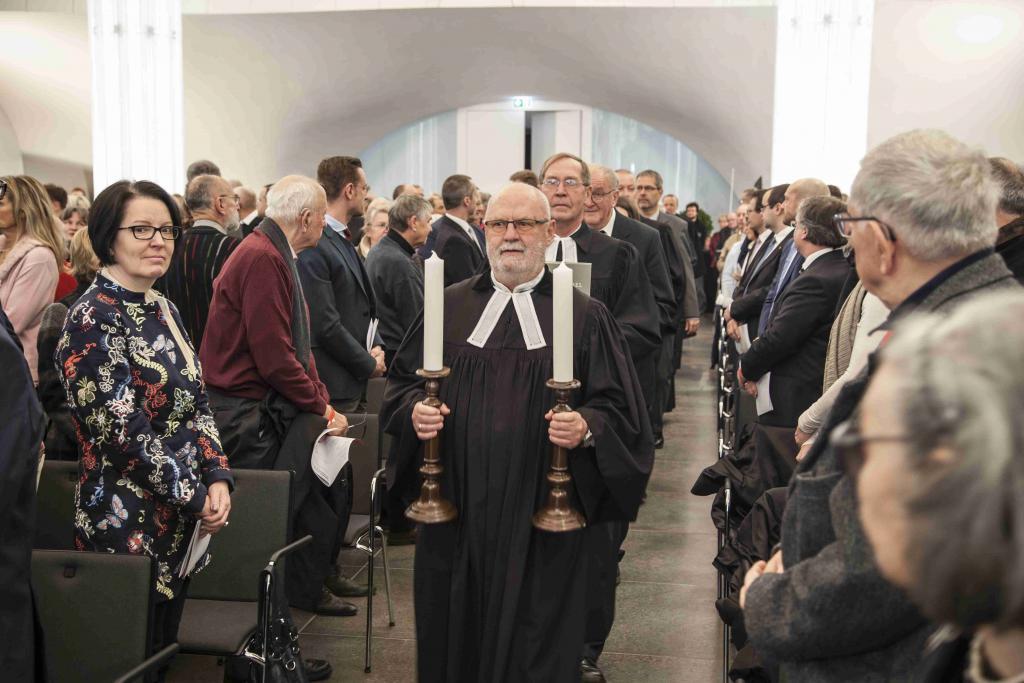 Pfarrer Nikolaus Krause trägt an der Spitze der Einziehenden die Leuchter in die neue Universitätskirche. Foto: Jan Adler