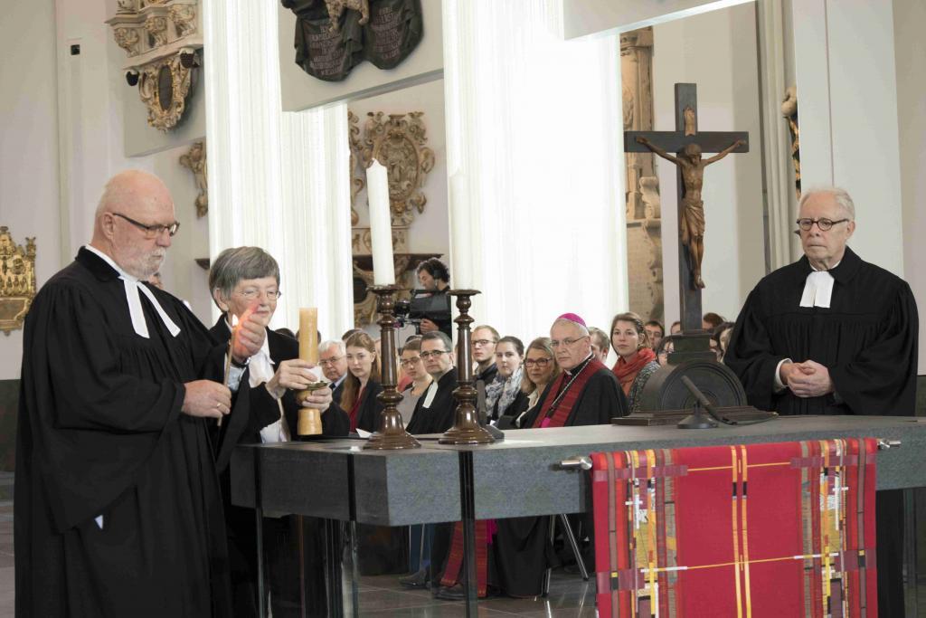 Zusammen mit Helga Hassenrück zündet Nikolaus Krause die Kerzen auf dem Altar an. Neben dem Altar steht der frühere Universitätsprediger Rüdiger Lux. Foto: Jan Adler