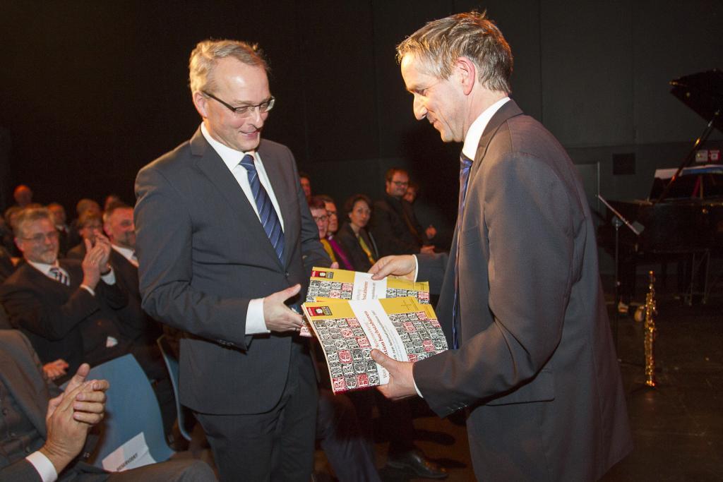 Carsten Rentzing (li.) erhält von Christoph Seele, Beauftragter der evangelischen Landeskirchen beim Freistaat Sachsen, die aktuelle Reformationsbroschüre überreicht