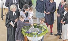 Taufe als Neugeburt im Glauben: In der Dorfkirche Lohmen (Sächsische Schweiz) wird ein Kind getauft. Die Schwester des Täuflings gießt das Wasser aus der Taufkanne in die Taufschale. Eltern und Paten begleiten die Zeremonie. Foto: epd-bild/Rainer Oettel